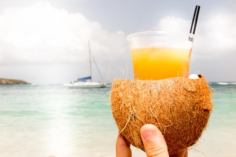 Coconut with drinking straw on beach at the sea in woman hand stock image