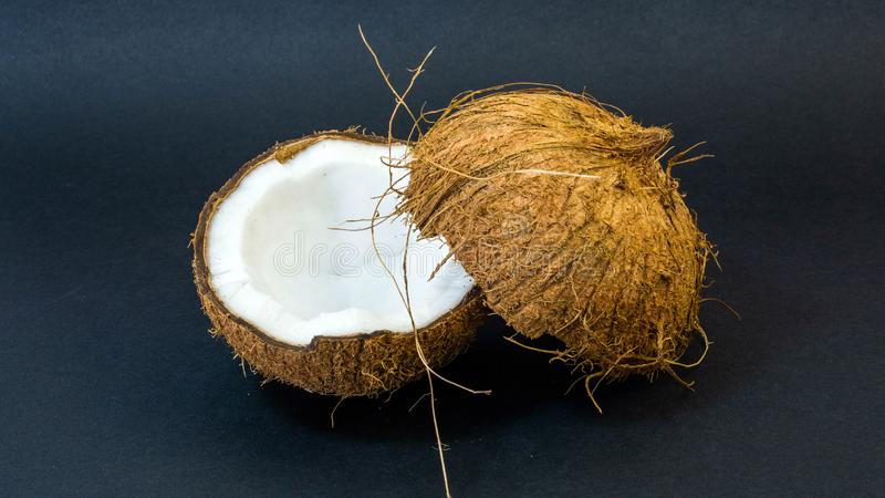 Coconut, exotic fruit, two halves of the fruit in the shell, dark background, selective focus, selective light, close-up royalty free stock image