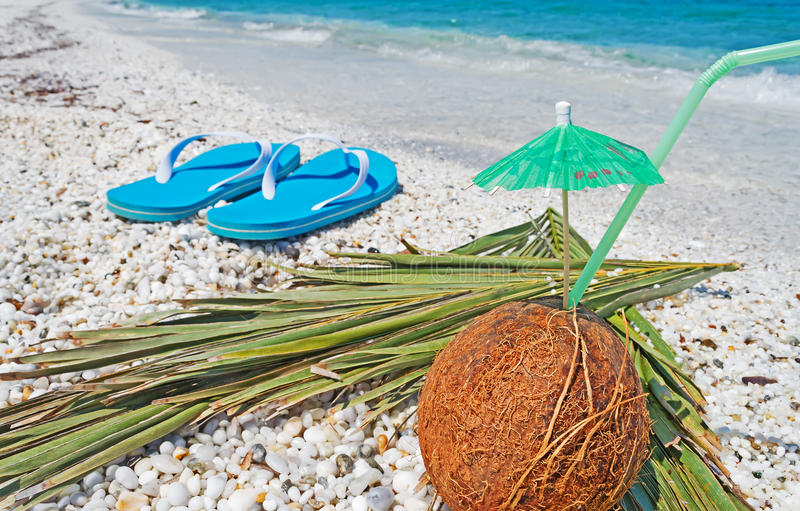 Coconut and flip flops. By the sea royalty free stock photos