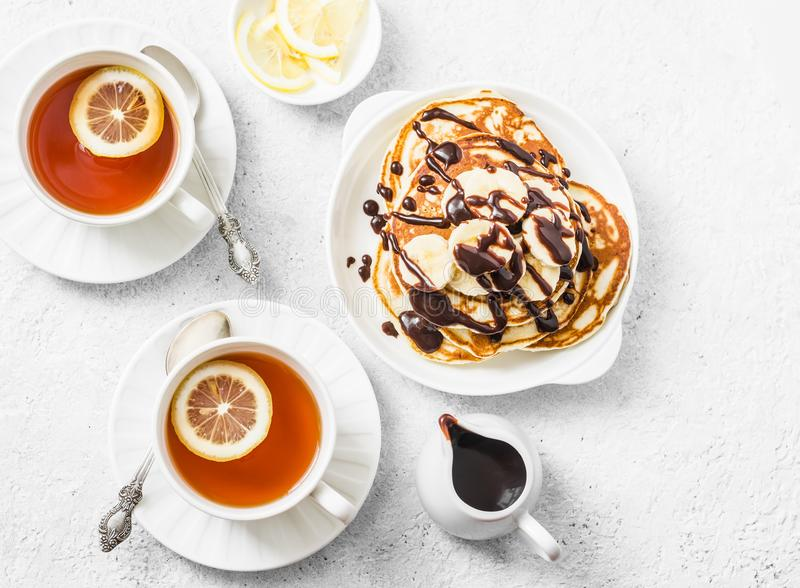 Coconut flour pancakes with banana and chocolate sauce and tea with lemon on a light background, top view. Delicious breakfast, de stock images