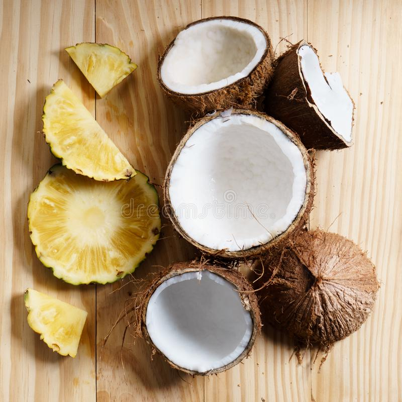 Coconut and fresh pineapple. Coconut with brown shell and sliced fresh pineapple, summer fruits, on wooden background stock images