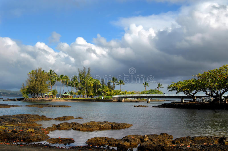 Coconut Island on Big Island. Storm clouds clear and the blue pops through over Coconut Island on the Big Island. A man gazes over the railing of the connecting royalty free stock images