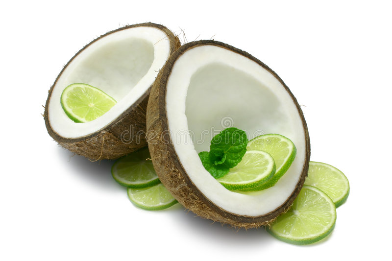 Coconut and Lime. Coconut halves with Lime slices and mint sprig, isolated on white royalty free stock photography