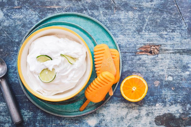 Coconut lime sorbet and orange popsicles with fresh fruits royalty free stock photos