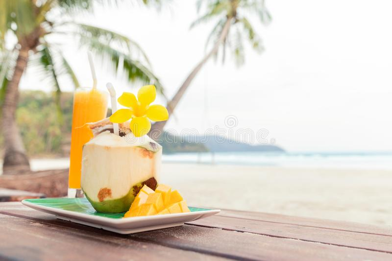 Coconut on Mango Background. Tropical Fruits. Summer Concept. Drink. Summer Concept. Still Life of Juice from Tropical Fruits. Summer Concept. Copy Space royalty free stock photography