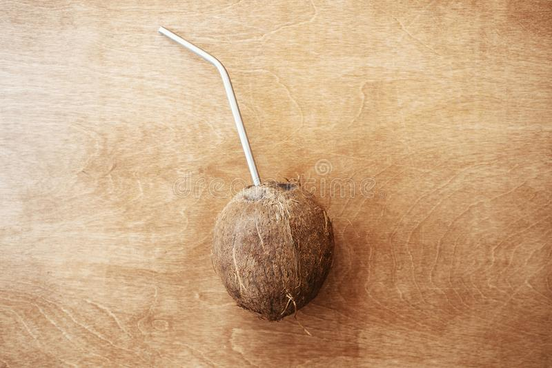 Coconut and metal straw on wooden table, flat lay. Hello summer vacation concept. Zero waste. Space for text. Ban plastic. royalty free stock image