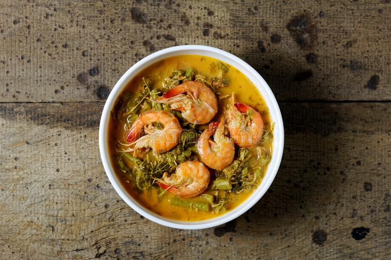 Coconut Milk Curry with young Tamarind Leaves and shrimp in bowl on wood table.Thai traditional food. Coconut Milk Curry with young Tamarind Leaves yardlong bean royalty free stock images