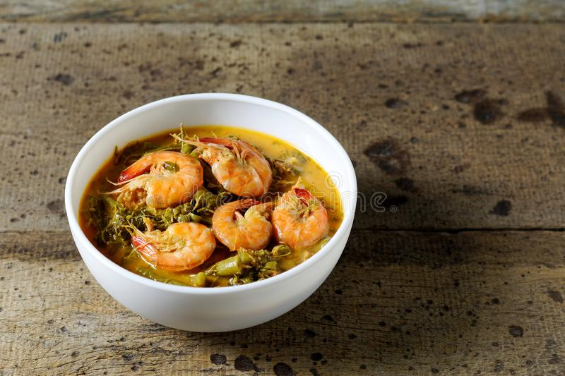 Coconut Milk Curry with young Tamarind Leaves and shrimp in bowl on wood table.Thai traditional food. Coconut Milk Curry with young Tamarind Leaves yardlong bean royalty free stock photography