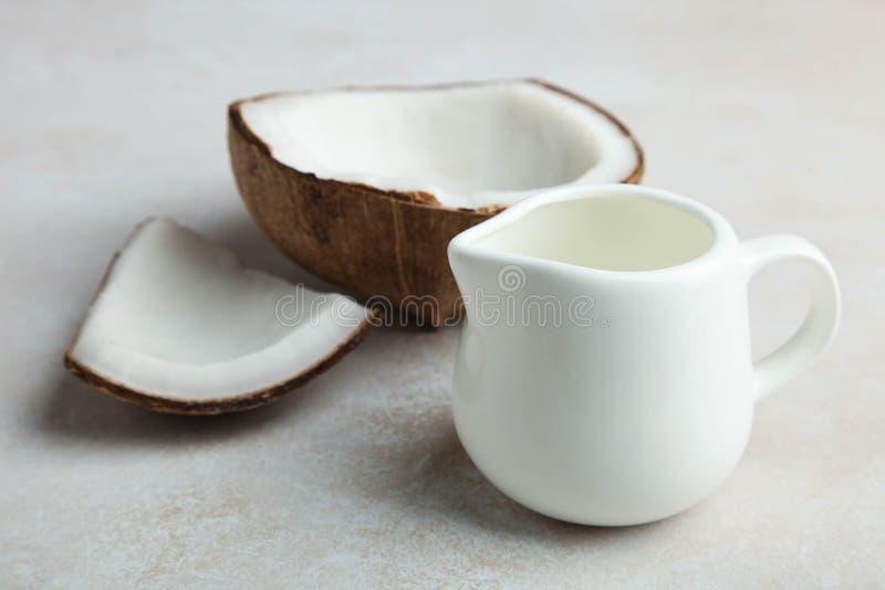 Coconut and coconut milk in milk jug. Broken natural exotic coconut and coconut milk in milk jug on neutral background stock photos