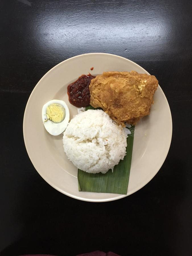 Coconut milk rice with boil egg, fried chicken and sambal. A top shot of coconut milk rice with boil egg, fried chicken and sambal served for breakfast royalty free stock photography