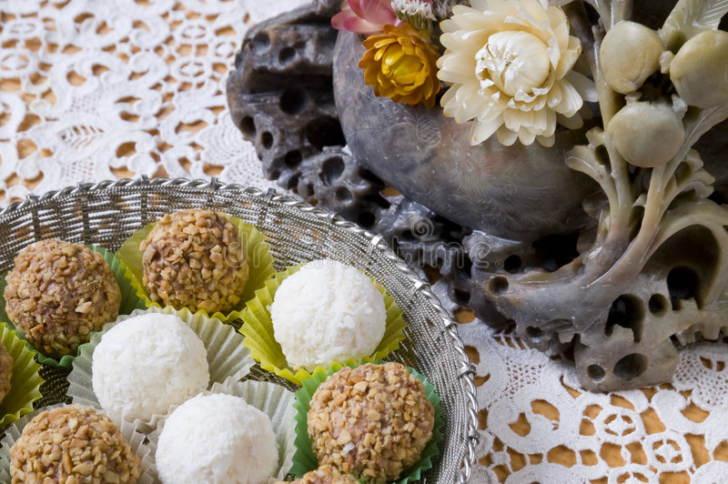 Coconut and nut candy. Silver bowl with coconut and nut candy on lace doily and old vase from stalagmites stock image