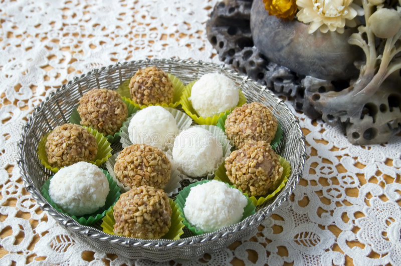 Coconut and nut candy. Silver bowl with coconut and nut candy on lace doily and old vase from stalagmites royalty free stock photos