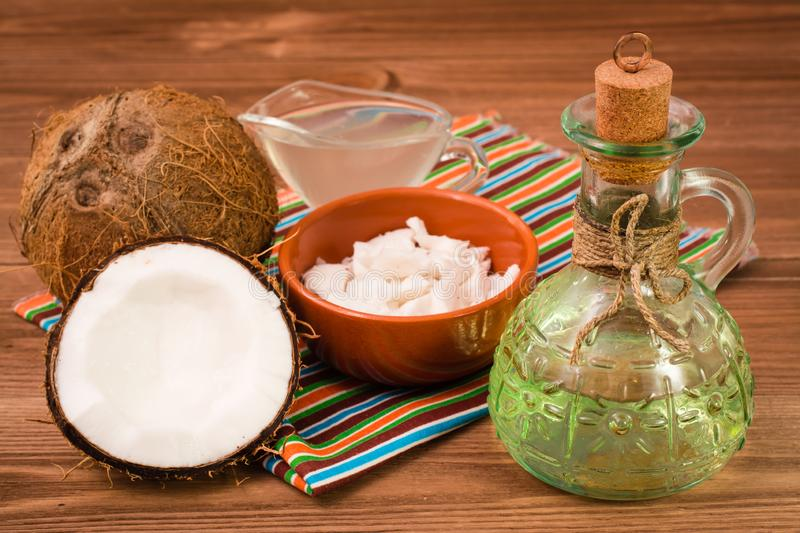 Coconut oil in a bottle, coconut milk and coconuts stock image