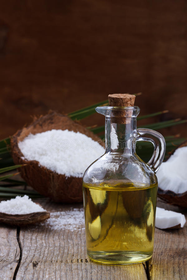 Coconut oil and coconut flakes. Coconut oil and coconut on old wooden background royalty free stock photography