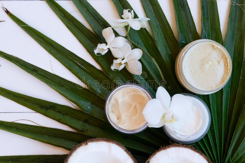 Coconut oil and cosmetics. With palm leaves close up on white wooden background stock photography