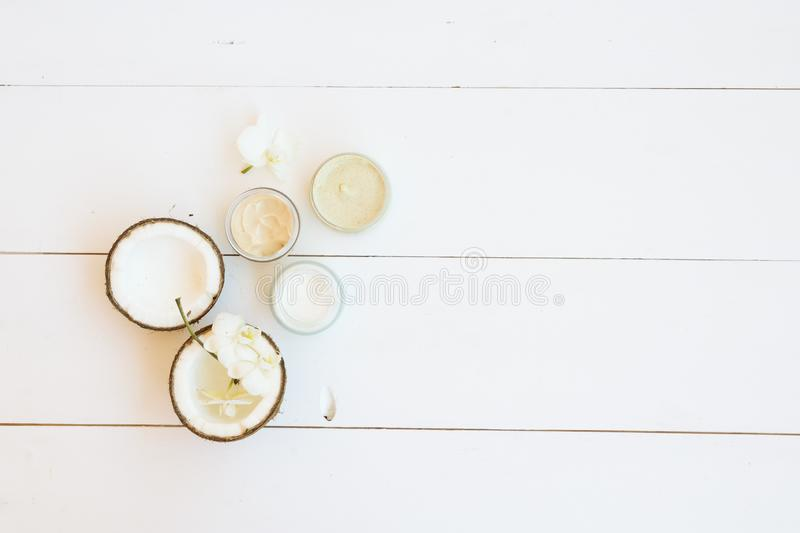 Coconut oil nd cosmetics. Coconut oil and cosmetics on white wooden planks background, top view royalty free stock images