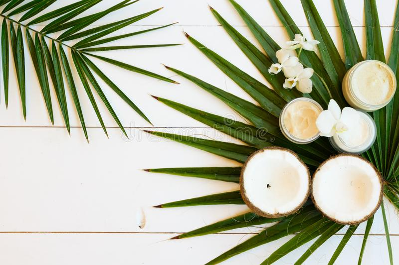 Coconut oil nd cosmetics. Coconut oil and natural cosmetics with green palm leaves close up on white wooden background royalty free stock photos