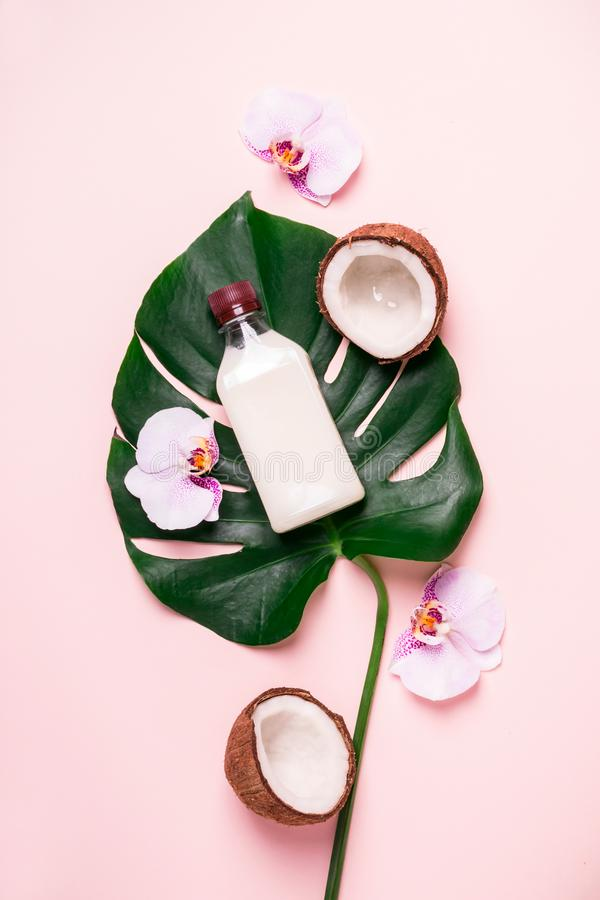 Coconut oil and tropical leaves and flowers. Hair care spa concept.  royalty free stock photography