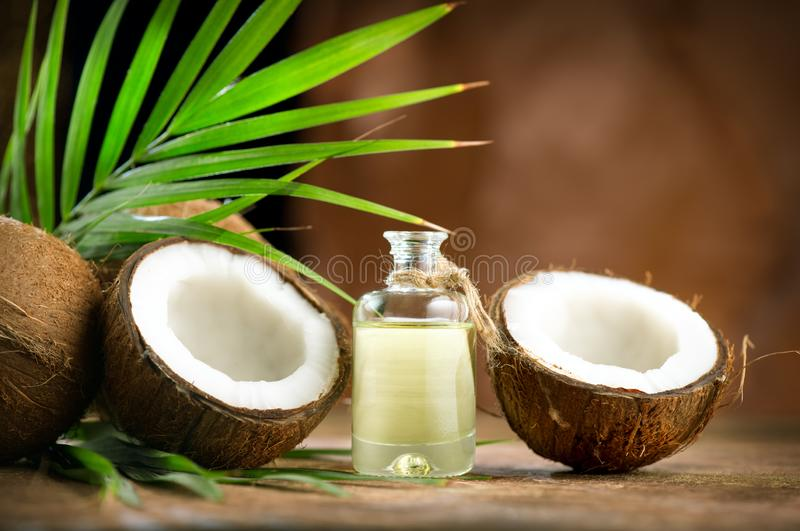 Coconut palm oil in a bottle with coconuts and green palm tree leaf on brown background. Coco nut closeup. Healthy food, skincare royalty free stock photo