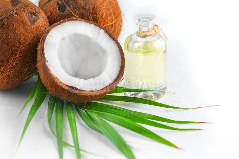 Coconut palm oil in a bottle with coconuts and green palm tree leaf isolated on a white background. Border design. Healthy Food. Skin care concept. Vegan food stock photo