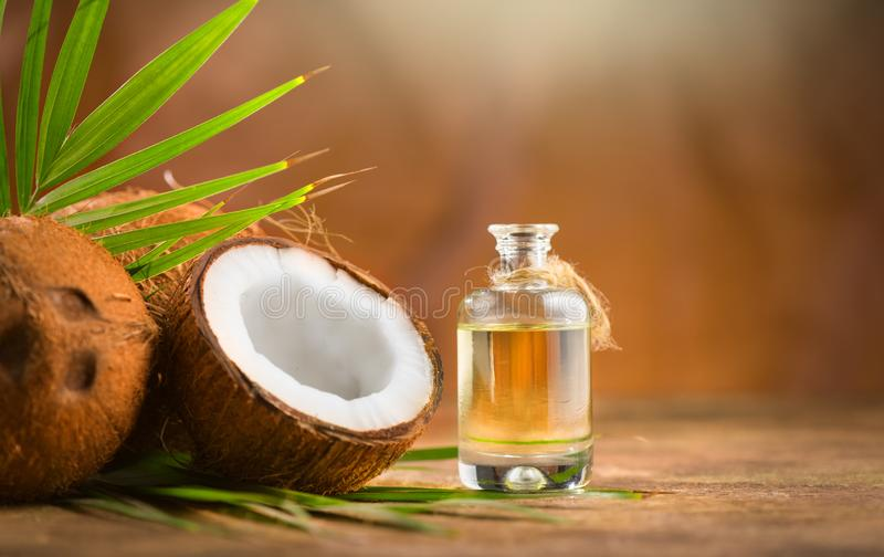 Coconut palm oil in a bottle with coconuts and green palm tree leaf on brown background. Coco nut closeup. Healthy Food, skin care. Concept. Vegan food stock image