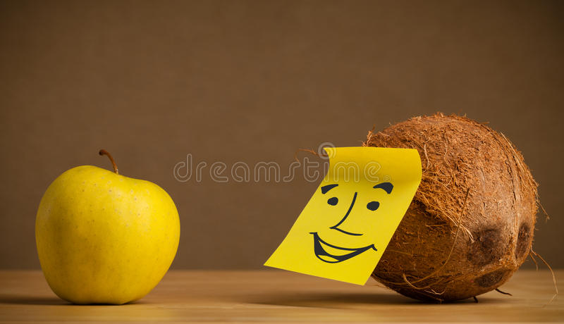 Coconut with post-it note smiling at apple. Coconut with sticky post-it note looking at citrus apple stock image