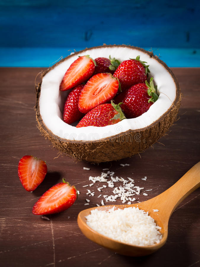Coconut and strawberries on wooden background royalty free stock images