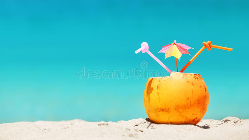 Coconut with straws and colorful cocktail umbrella on a tropical royalty free stock photo