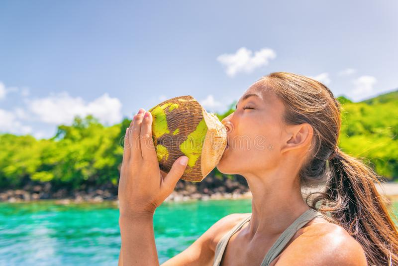 Coconut water Caribbean tropical food tourist woman drinking fresh natural from the coco on cruise ship travel vacation. Asian royalty free stock image