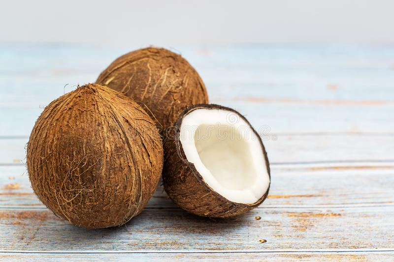 Coconut. Whole and half on light wooden background. Side view stock image