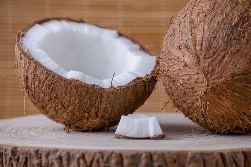 Coconut whole, half and piece on brown natural background stock photos