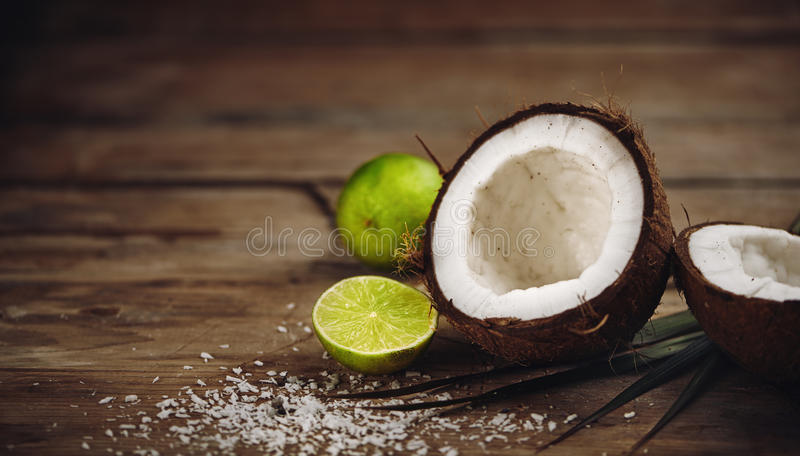 Coconut on wooden table. Close-up of fresh coconut and sliced lime on wooden table stock photography