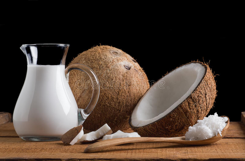 Coconuts and coconut milk. Coconut and coconut milk on old wood table stock image