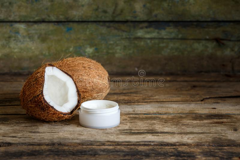 Coconuts with cosmetics cream on wooden background royalty free stock images