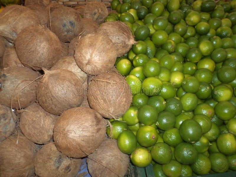 Coconuts and lemons, in market stall royalty free stock photo