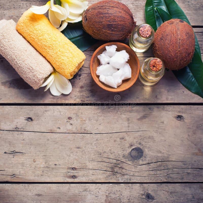 Cocos, óleo de coco e toalhas no fundo de madeira do vintage fotografia de stock