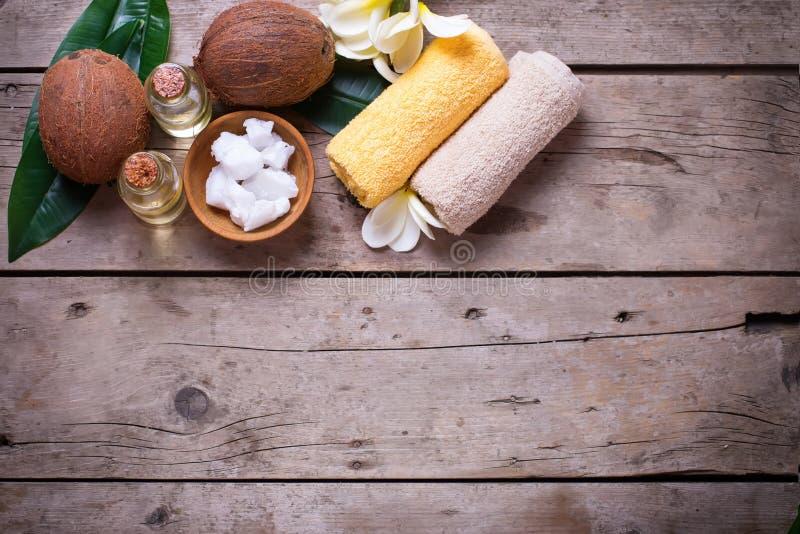 Cocos, óleo de coco e toalhas no fundo de madeira do vintage fotos de stock