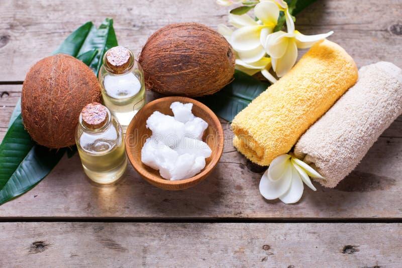 Cocos, óleo de coco e toalhas no fundo de madeira do vintage imagem de stock royalty free
