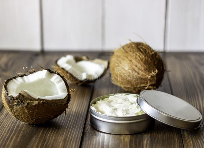 Cocos e óleo de coco em um potenciômetro do metal Fundo de madeira imagens de stock