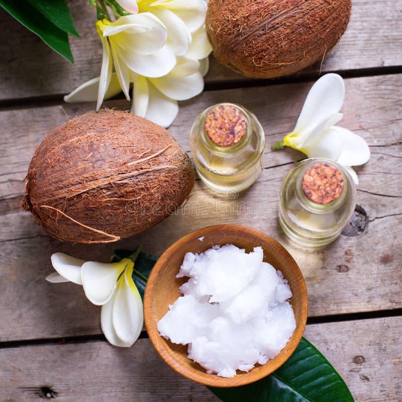 Cocos e óleo de coco no fundo de madeira do vintage fotos de stock