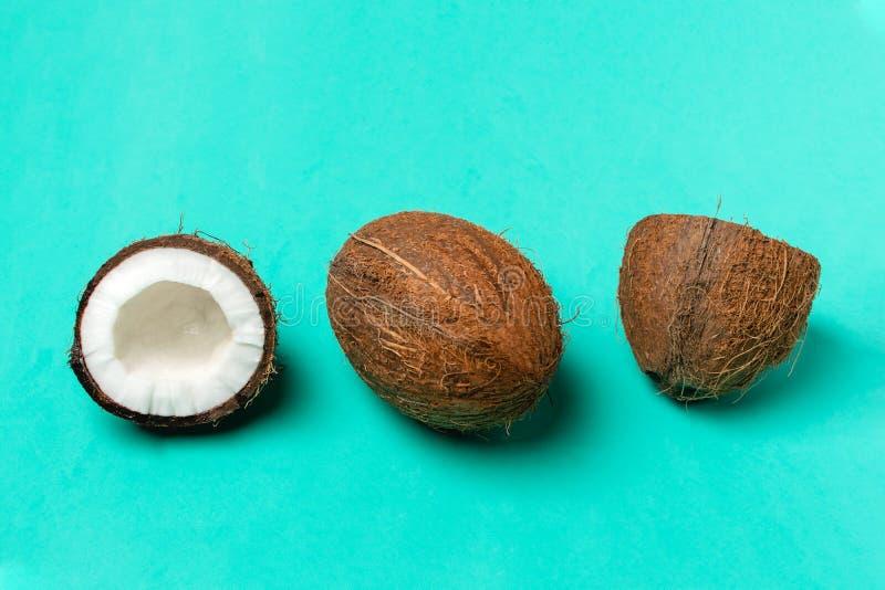 Cocos e coco maduros da metade no fundo azul brilhante, composição mínima, conceito do fruto tropical, configuração lisa, pop art foto de stock