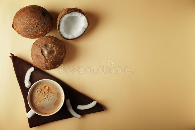 Cocos e xícara de café maduros no fundo da cor foto de stock royalty free