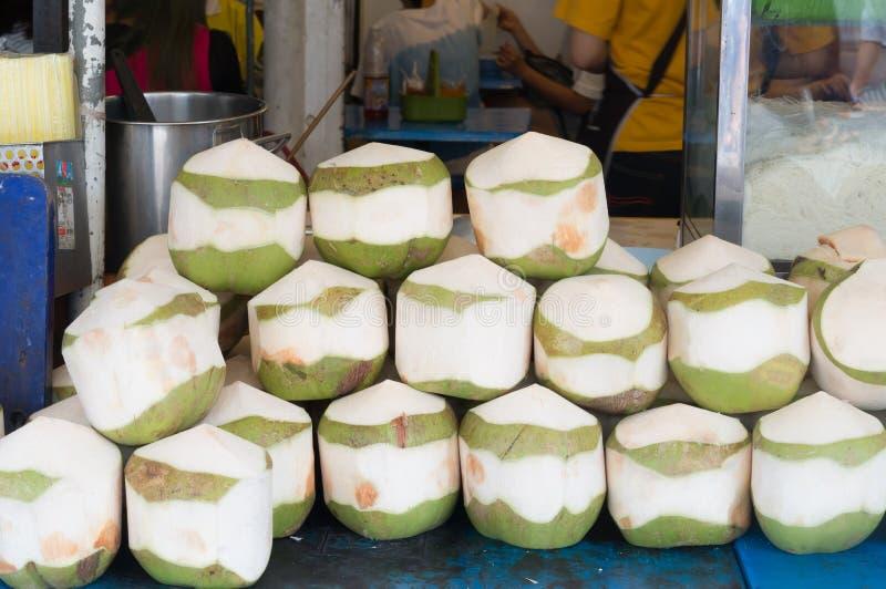 Cocos pelados jóvenes apilados en orden en venta foto de archivo libre de regalías