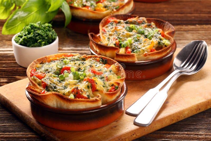 Cocotte en terre avec du fromage, des épinards et des tomates photos stock