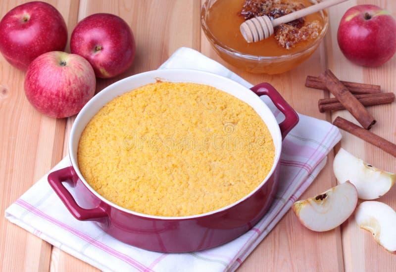 Cocotte en terre de couscous avec les pommes, le miel et la cannelle photographie stock libre de droits