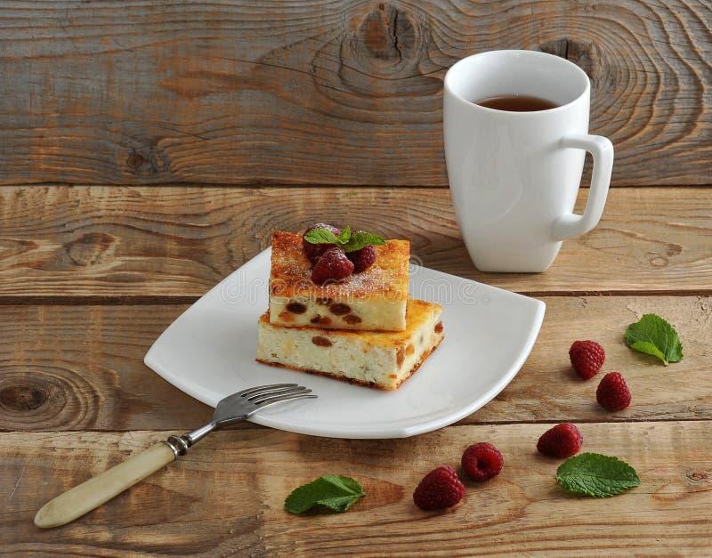 Cocotte en terre de fromage blanc avec des raisins secs et une tasse de thé images libres de droits