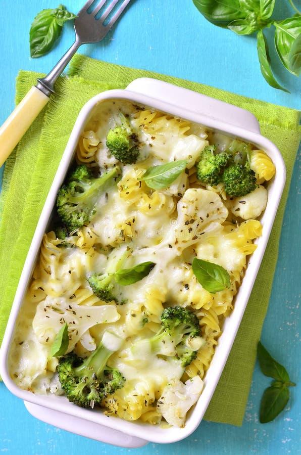 Cocotte en terre de pâtes avec le brocoli, le chou-fleur et le fromage image stock