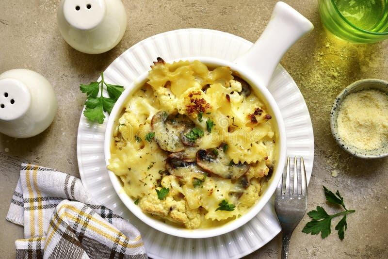Cocotte en terre de pâtes avec les champignons et le chou-fleur à une sauce crème photos stock