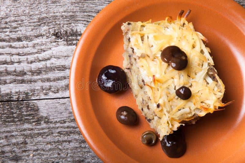 Cocotte en terre de pomme de terre avec les champignons salés dans un plat d'argile sur le vieil OE image stock