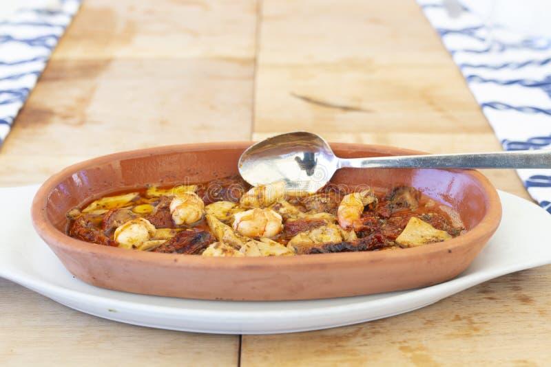Cocotte en terre méditerranéenne de crevettes et de crevettes roses sur le bois image stock